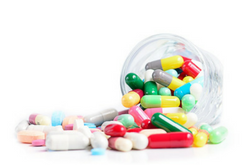 Image of assorted pills spilling from bottle